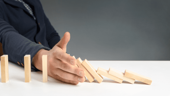 consulting jobs during recession. Image is of someone putting their hand in a row of dominoes to stop them from falling.