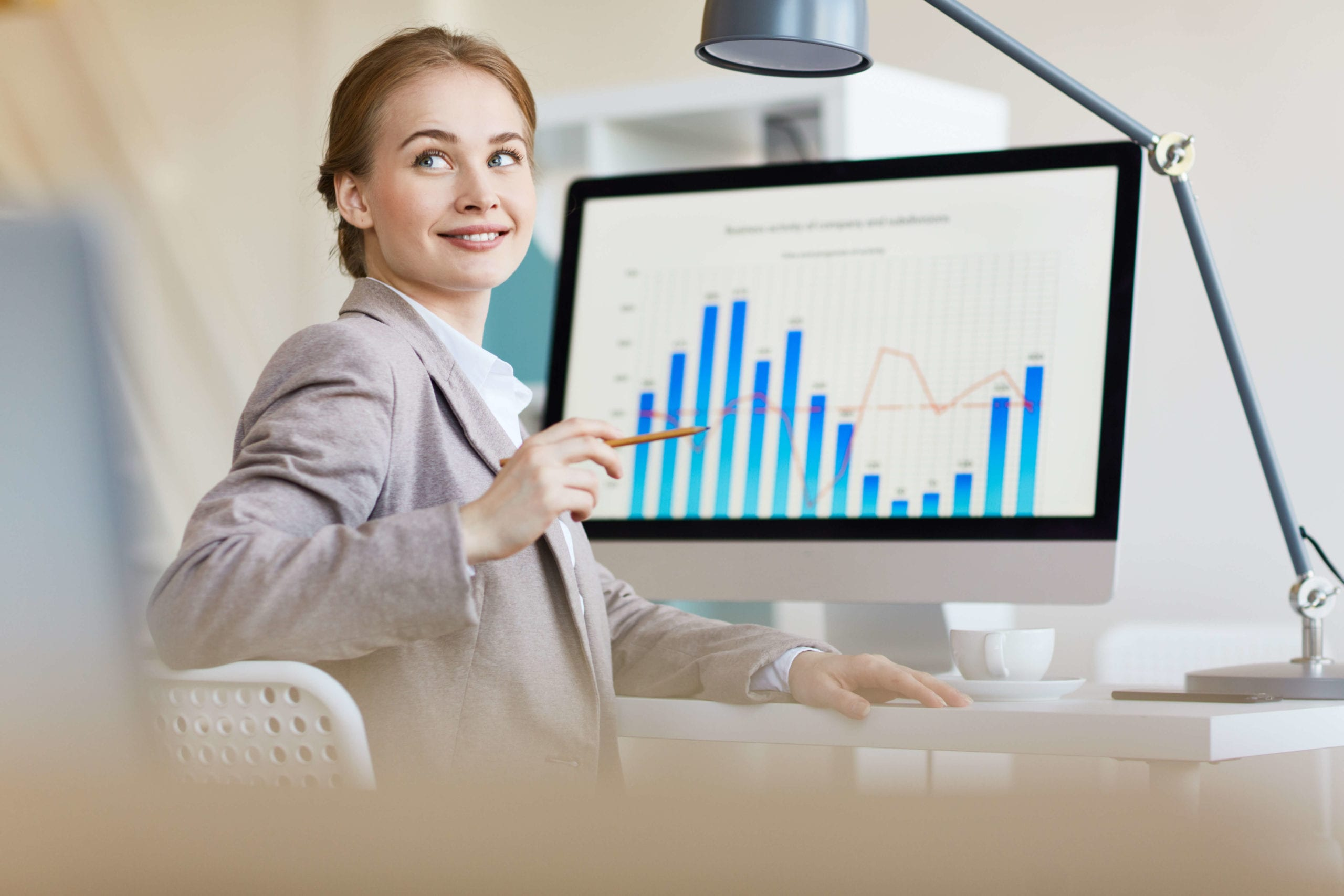 What is BCG Gamma? This image shows a woman in a suit looking at a bar chart on a computer.