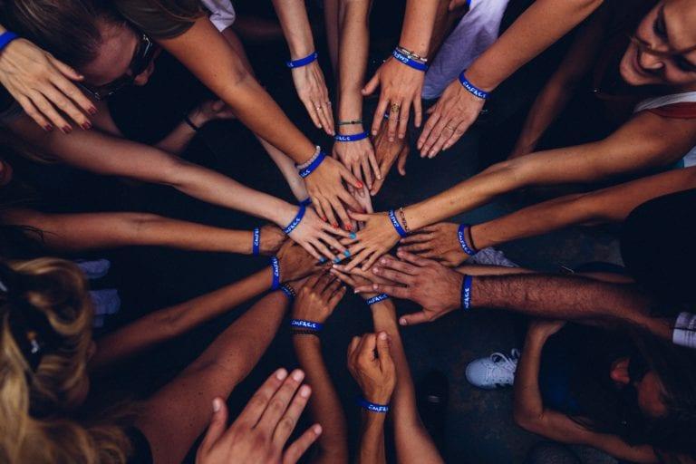 Case frameworks. Picture depicts 2 dozen hands all pulled in for a teamwork huddle.