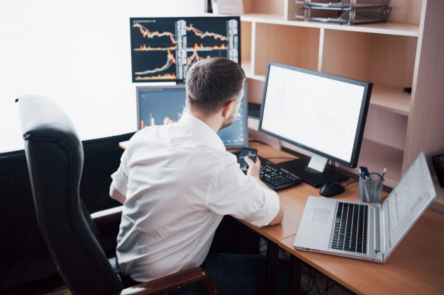 Market entry case. this image shows a consultant working in an office with graphs on multiple PC screens.