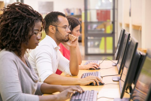 Bain online multiple choice test. Image shows a row of 3 people taking tests on computers at a college library.