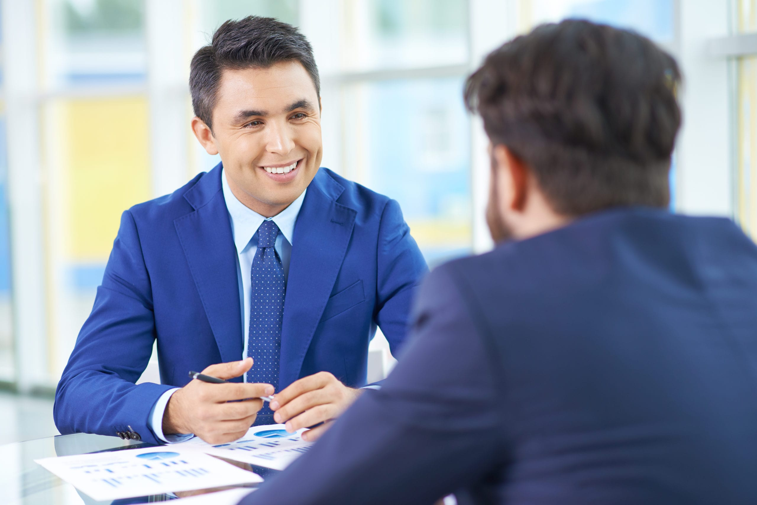 Bain Experience Interview. Picture depicts two men wearing blue business suits in a meeting.