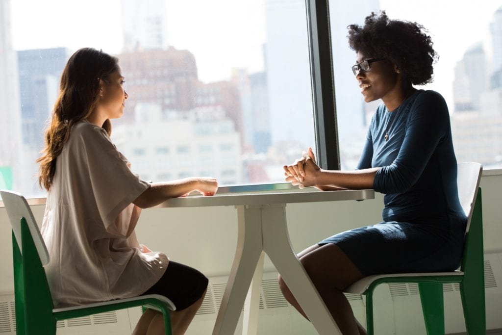 IQVIA Careers. This picture depicts two women having a business conversation with tall buildings in the background.