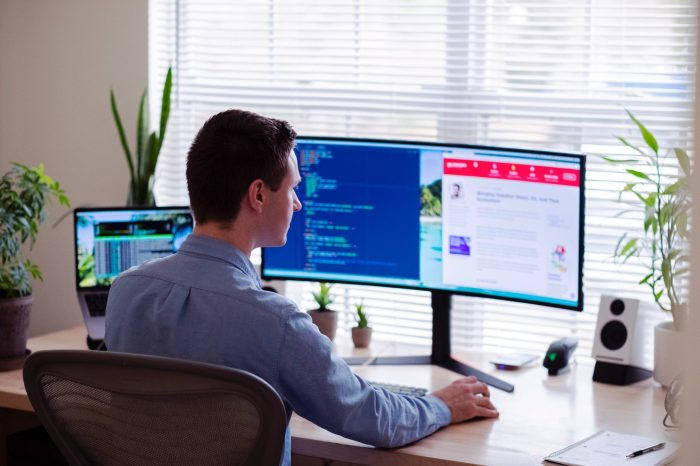 online case interview. This image shows a man in a button-down shirt sitting in his office looking at a wide-screen computer monitor.