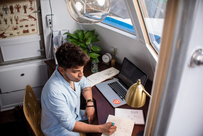 Case Interview Video Conference. This image shows a college student sitting at the desk in his dorm in front of a laptop, preparing for his virtual interview.