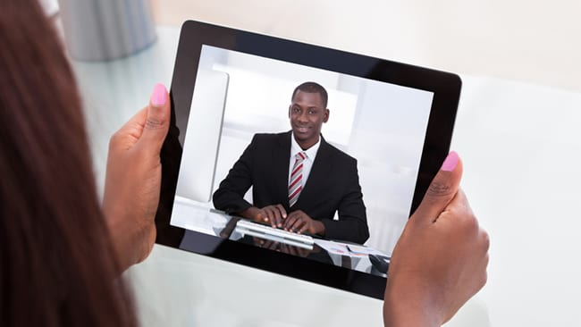 One way video interview Bain. Picture depicts a consulting candidate in a suit on an iPad screen.